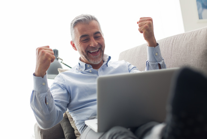 Cheerful businessman lying on the couch at home and using a laptop, he is joyful and raising his fists