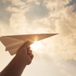 Taking flight! hand holding paper airplane in the sky.